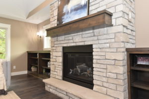 Stone surround gas fireplace with stone hearth and custom wood mantle
