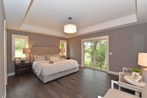 Master suite bedroom with warm tones and tray ceiling