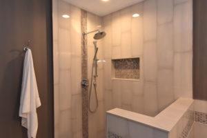 Beautifully tiled master bathroom shower with Delta plumbing fixtures