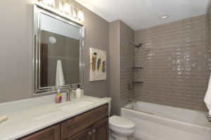 Bathroom with grey subway tile and stained vanity