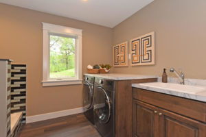 Laundry room with white trim and wood stain cherry cabinets