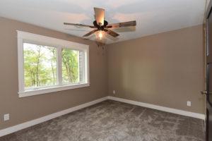 Basement bedroom with white trim overlooking wooded backyard