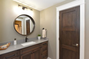 Basement bathroom with white trim and dark stain doors and cabinets